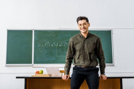 Photo for Smiling male teacher in formal wear looking at camera and standing near desk in classroom - Royalty Free Image