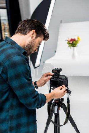 Photo pour Beau jeune homme photographier de belles fleurs en studio photo professionnel - image libre de droit