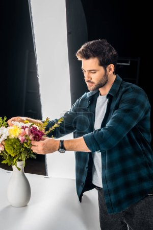 handsome young man arranging flowers in professional photo studio