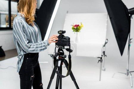 Foto de Recortar foto de joven mujer fotógrafo tirar flores en estudio - Imagen libre de derechos