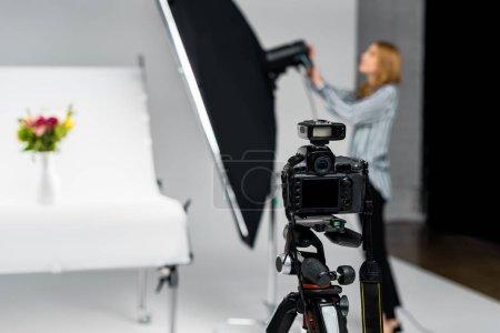 Photo pour Vue rapprochée de l'appareil photo et la jeune femme travaillant avec matériel d'éclairage en studio - image libre de droit