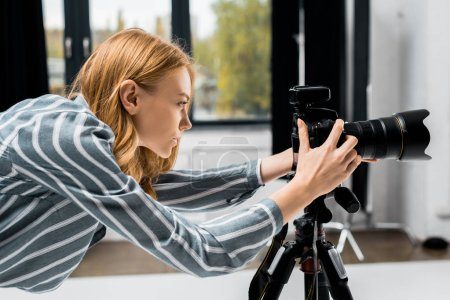 Photo for Side view of young female photographer working with professional photo camera in studio - Royalty Free Image