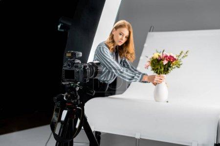 Photo pour Vue rapprochée de l'appareil photo et photographe femme organisant des fleurs en studio - image libre de droit