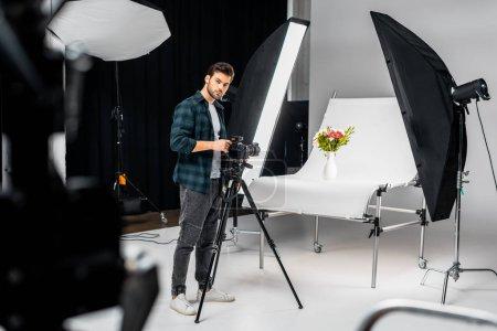 Photo pour Beau jeune photographe travaillant avec appareil photo et matériel d'éclairage en studio photo - image libre de droit