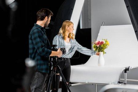 Photo pour Jeunes photographes professionnels photographiant de belles fleurs en studio photo - image libre de droit