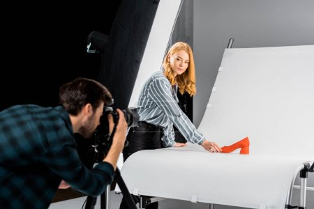 Photo for Male photographer working with camera while colleague arranging shoe in studio - Royalty Free Image