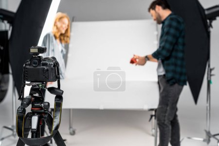 Photo for Close-up view of professional photo camera and photographers working behind in studio - Royalty Free Image