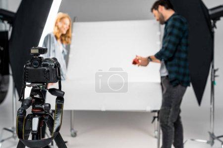Photo pour Vue rapprochée de l'appareil photo professionnel et photographes travaillant derrière en studio - image libre de droit