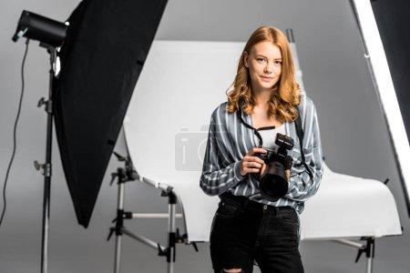 Photo pour Belle jeune femme photographe travaillant en studio photo professionnel - image libre de droit