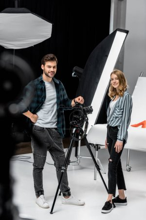Photo for Happy young photographers standing together and smiling at camera in photo studio - Royalty Free Image