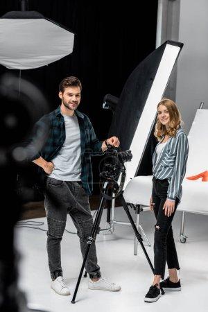 Photo pour Heureux jeunes photographes rassemblés et souriant à la caméra en studio photo - image libre de droit