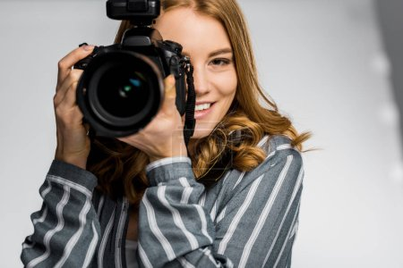 beautiful smiling girl using photo camera in studio