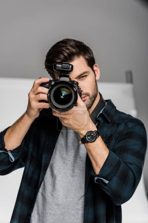 Photo for Handsome young male photographer shooting with professional camera - Royalty Free Image
