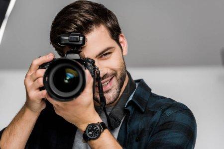 Photo pour Beau jeune homme heureux photographier avec appareil photo en studio - image libre de droit
