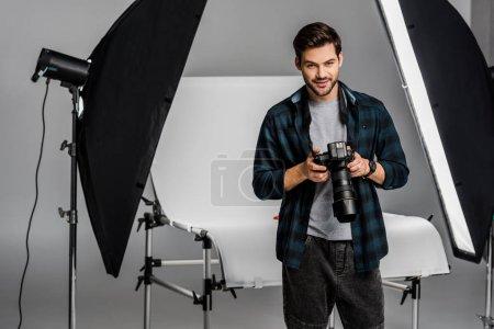 Photo pour Beau jeune photographe professionnel souriant à la caméra tout en travaillant dans un studio photo - image libre de droit