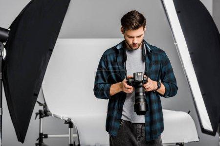 Photo pour Beau jeune photographe professionnel utilisant l'appareil photo en studio - image libre de droit
