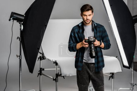 Photo for Handsome professional young photographer using camera in photo studio - Royalty Free Image