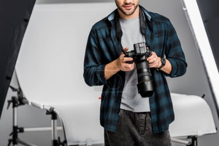 Photo for Cropped shot of professional young photographer using camera in photo studio - Royalty Free Image