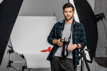 Photo for Handsome professional young photographer looking at camera in studio - Royalty Free Image
