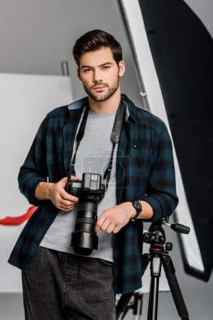 handsome professional young photographer looking at camera in photo studio