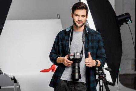 Photo pour Beau jeune photographe souriant tenant la caméra et montrant pouce vers le haut en studio - image libre de droit