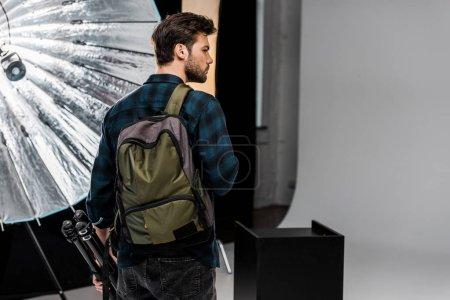 Photo pour Vue arrière du jeune homme avec sac à dos tenant équipement professionnel et regardant loin dans le studio de photo - image libre de droit