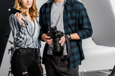 cropped shot of young photographers holding camera and light meter in studio