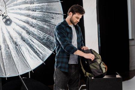 Foto de Joven fotógrafo profesional equipo del embalaje en mochila - Imagen libre de derechos