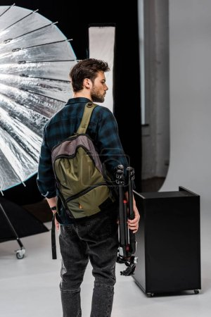 Photo for Back view of young man with backpack holding professional equipment in photo studio - Royalty Free Image