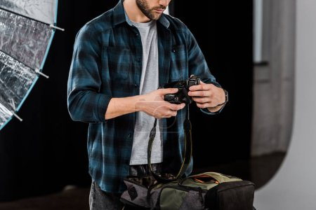 Photo for Cropped shot of professional young photographer packing camera in backpack in photo studio - Royalty Free Image