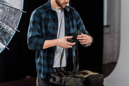 Photo pour Recadrée tir professionnel jeune photographe emballage caméra dans le sac à dos en studio photo - image libre de droit