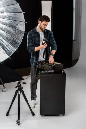 Photo for Professional young photographer packing camera in backpack in photo studio - Royalty Free Image