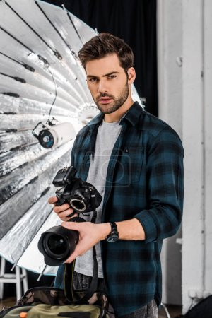 handsome professional young photographer holding camera and lens in studio