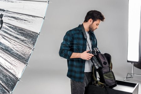 professional young photographer holding camera and backpack with photo equipment in studio