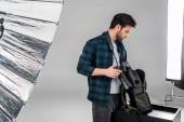 """Постер, картина, фотообои """"профессиональный фотограф молодых, держа камеру и рюкзак с фото оборудования в студии"""""""