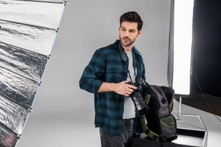 handsome professional young photographer standing with photo camera and looking away in studio