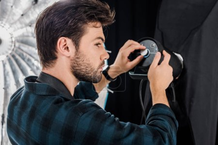 young photographer working with professional lighting equipment in photo studio