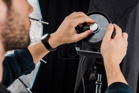 Photo pour Recadrée tir du jeune homme, travaillant avec des appareils d'éclairage professionnel en studio photo - image libre de droit