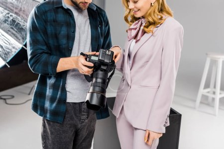 cropped shot of smiling young photographer and model using photo camera together