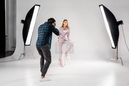 Photo pour Vue arrière du photographe belle jeune femme mannequin en studio photo - image libre de droit
