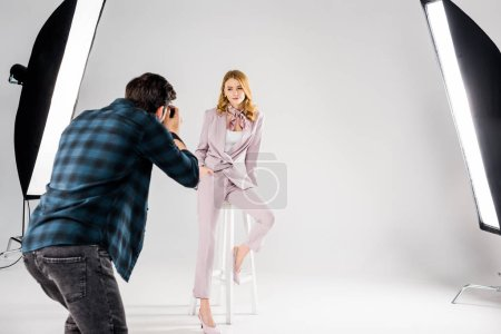 back view of photographer shooting beautiful young female model in studio
