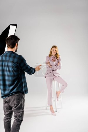 Photo for Back view of young photographer talking with beautiful smiling female model in studio - Royalty Free Image