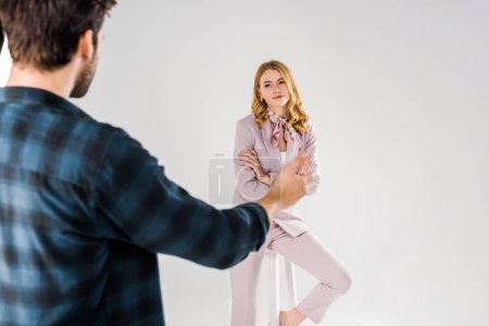 Photo pour Recadrée tir du photographe parlant avec beau modèle féminin en studio - image libre de droit