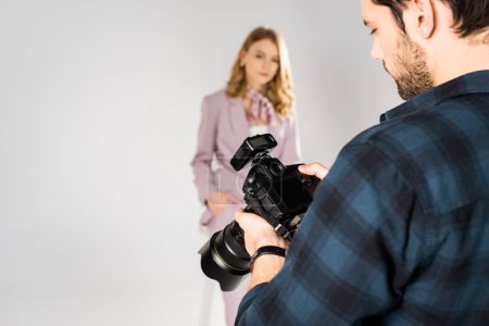 cropped shot of photographer using camera and model posing in photo studio
