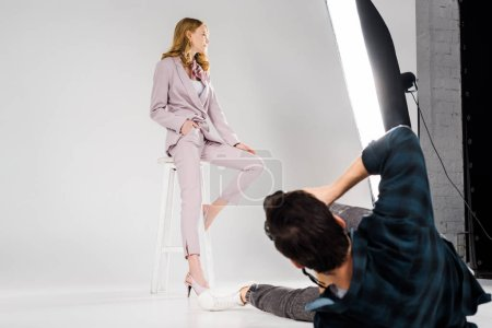 young photographer lying and shooting beautiful female model posing in photo studio