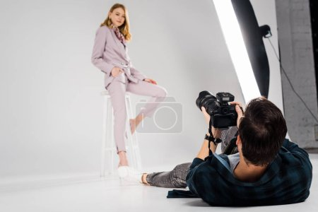 photographer lying and shooting beautiful female model posing in studio