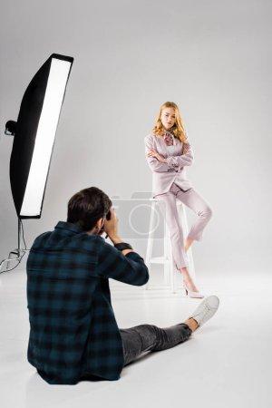 Photo pour Vue arrière du photographe assis et photographier le beau modèle féminin qui pose en studio - image libre de droit