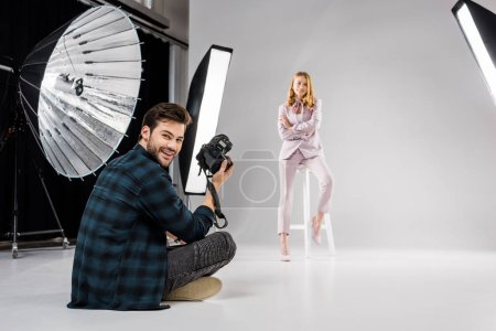 Photo for Photographer sitting and smiling at camera while beautiful female model posing in studio - Royalty Free Image