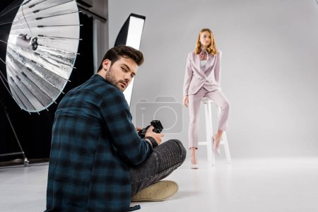 photographer sitting and looking at camera while beautiful female model posing in studio