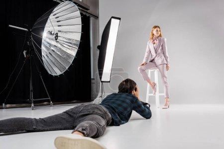 Photo pour Photographe couché et le tir de beau modèle féminin en studio photo - image libre de droit
